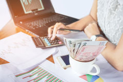 Donna di affari che conta soldi e che analizza rapporto finanziario del grafico con il calcolatore ed il taccuino sullo scrittori Fotografie Stock Libere da Diritti