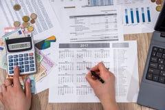 Donna di affari che conta sul bilancio domestico annuale del calcolatore immagine stock