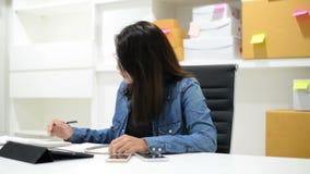 Donna di affari che controlla le fatture e che fa bilancio con il calcolatore video d archivio