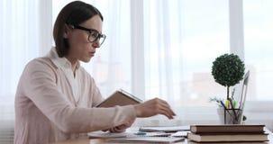 Donna di affari che controlla le note mentre per mezzo del computer portatile stock footage