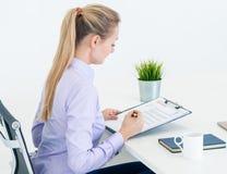 Donna di affari che controlla un'intervista di lavoro del riassunto del documento fotografia stock libera da diritti