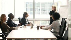 Donna di affari che dà presentazione ai colleghi multi-etnici alla riunione nella sala del consiglio video d archivio