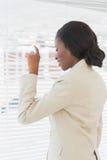 Donna di affari che dà una occhiata attraverso i ciechi in ufficio fotografia stock libera da diritti