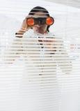 Donna di affari che dà una occhiata con il binocolo attraverso i ciechi immagini stock libere da diritti
