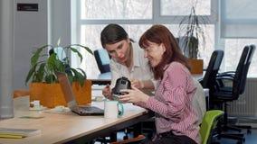 Donna di affari che discute gli occhiali di protezione che di realtà virtuale sta usando con un collega archivi video