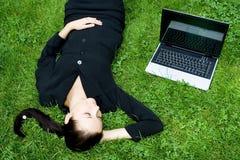 Donna di affari che dorme al lato di un computer portatile Fotografie Stock Libere da Diritti