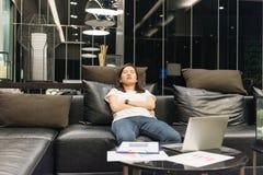 Donna di affari che dorme sul sofà in salone alla notte Fotografia Stock