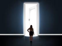 Donna di affari che esamina grande porta aperta luminosa Fotografie Stock Libere da Diritti