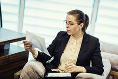 Donna di affari che esamina i documenti in cartella nell'ufficio, donna immagine stock