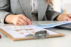 Donna di affari che esamina i grafici Fotografie Stock Libere da Diritti