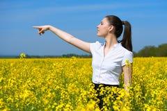 Donna di affari che esamina la distanza ed il punto Ragazza nel giacimento di fiore giallo Bello paesaggio della molla, da solegg Fotografia Stock