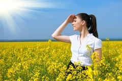 Donna di affari che esamina la distanza Ragazza nel giacimento di fiore giallo Bello paesaggio della molla, giorno soleggiato lum Immagini Stock Libere da Diritti
