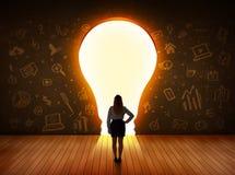 Donna di affari che esamina la lampadina della luce intensa nella parete Immagini Stock Libere da Diritti