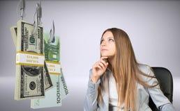 Donna di affari che esamina pacco di soldi Fotografia Stock
