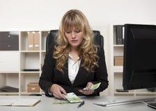 Donna di affari che esclude soldi al suo scrittorio Immagine Stock