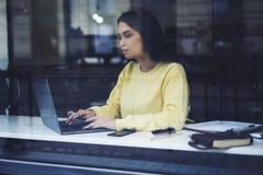 Donna di affari che fa lavoro a distanza che controlla documentazione finanziaria tramite computer portatile Fotografia Stock Libera da Diritti