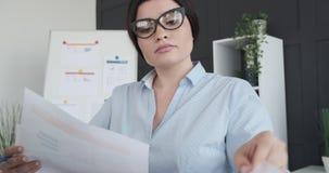 Donna di affari che fa lavoro di ufficio all'ufficio archivi video