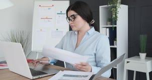 Donna di affari che fa lavoro di ufficio alla scrivania stock footage