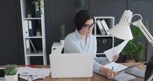 Donna di affari che fa lavoro di ufficio e che per mezzo del computer portatile all'ufficio archivi video