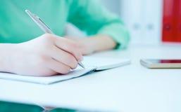 Donna di affari che fa le note con la penna nel luogo di lavoro dell'ufficio Immagini Stock Libere da Diritti
