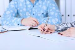 Donna di affari che fa le note nel luogo di lavoro dell'ufficio con il collega maschio ai precedenti Offerta di lavoro di affari, Fotografie Stock