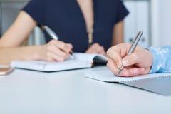 Donna di affari che fa le note nel luogo di lavoro dell'ufficio con il collega sui precedenti Equipaggi la lettera di scrittura,  Immagini Stock