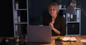 Donna di affari che fa videoconferenza a tarda notte all'ufficio video d archivio