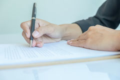Donna di affari che firma un contratto (fuoco selettivo) Immagine Stock