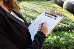 Donna di affari che firma una polizza dell'assicurazione auto sulla via Fotografia Stock Libera da Diritti