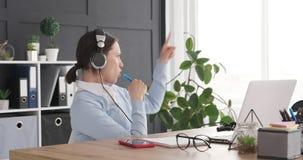 Donna di affari che gode mentre ascoltando e cantando musica nel luogo di lavoro stock footage