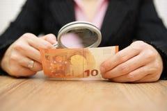 Donna di affari che guarda attraverso i soldi della lente d'ingrandimento frode co Fotografia Stock Libera da Diritti