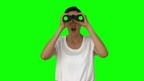 Donna di affari che guarda con il binocolo archivi video