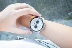 Donna di affari che guarda il suo orologio della mano fotografia stock libera da diritti