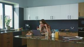 Donna di affari che ha chiacchierata al computer in cucina Persona di sorriso che parla online archivi video