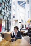 Donna di affari che ha intervallo per il caffè con il computer portatile Immagini Stock