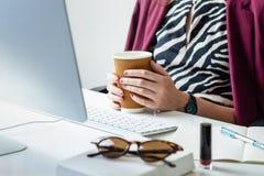 Donna di affari che ha tazza di caffè allo scrittorio in offi minimalistic immagini stock libere da diritti