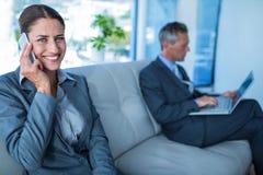 Donna di affari che ha telefonata mentre il suo collega che per mezzo del computer portatile Fotografia Stock