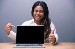 Donna di affari che indica sullo schermo in bianco del computer portatile fotografia stock