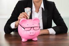 Donna di affari che inserisce banconota nel porcellino salvadanaio fotografie stock
