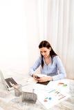 Donna di affari che invia gli sms nel frattempo che lavorano immagine stock
