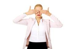 Donna di affari che la copre occhi di sue mani Non vedi concetto diabolico immagini stock