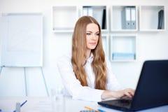Donna di affari che lavora ad un computer portatile all'ufficio Immagine Stock