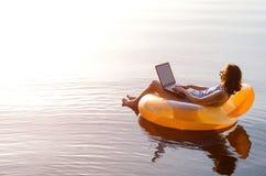 Donna di affari che lavora ad un computer portatile in un anello gonfiabile in fotografia stock libera da diritti