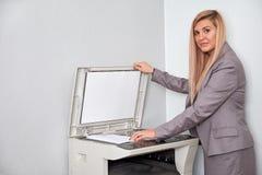 Donna di affari che lavora ad una macchina della copia all'ufficio fotografie stock