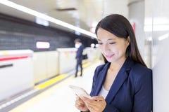 Donna di affari che lavora al cellulare in binario del treno immagini stock
