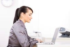 Donna di affari che lavora al computer portatile Fotografie Stock Libere da Diritti