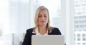 Donna di affari che lavora al computer portatile video d archivio