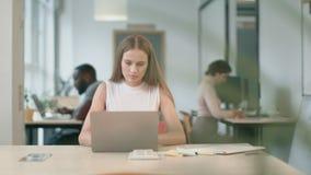 Donna di affari che lavora al computer portatile a coworking Ritratto di signora concentrata video d archivio