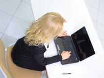 donna di affari che lavora al computer portatile nell'ufficio immagini stock libere da diritti