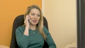 Donna di affari che lavora al computer di ufficio e che prende fine mobile di chiamata stock footage